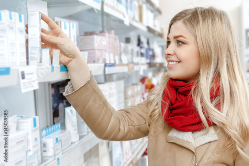 Attractive young female customer shopping at the drugstore