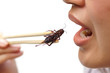 Asian female eating cricket - Eating insect concept