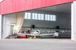 Small aircraft in open hangar