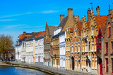 Panorama with canal and colorful traditional houses against blue sky in Brugge, Belguim