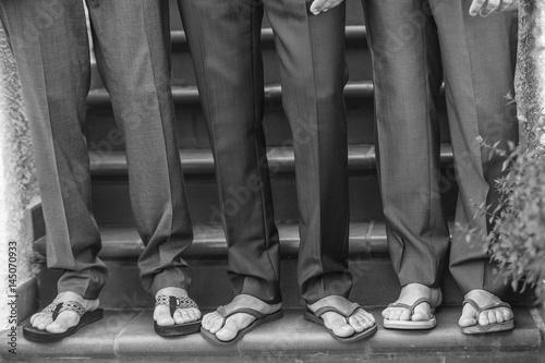 dettaglio piedi di 3 uomini con pantaloni eleganti e infradito Poster