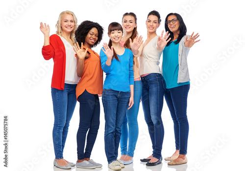 international group of happy women waving hands