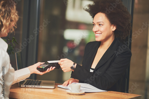 Young businesswoman paying with credit card in cafeteria, smile on the face Poster