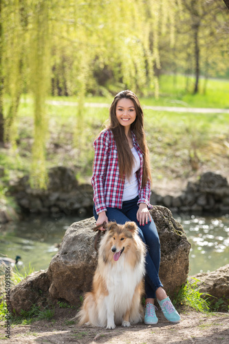 Poster young beautiful woman with long hair walking with collie dog