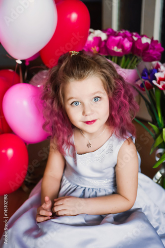 Poster Little beautiful sweet girl with pink curly hair in a silver dress in red tulips and with multi-colored balls smiling and posing