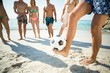 Man balancing soccer ball against friends
