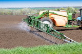 The tractor fertilizes the field, the genetically modified products