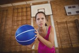 High school girl playing basketball in the court