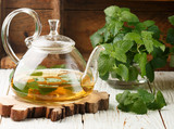 Herbal tea in a transparent teapot on the table and sprigs of fresh Melissa (lemon balm) and mint. Selective focus - 145133120