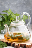 Herbal tea with Melissa and mint on the table in a transparent teapot. Selective focus - 145133161
