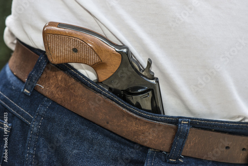 Poster Pistol for personal protection stored in waist of pants