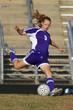 Female soccer player taking a shot on goal
