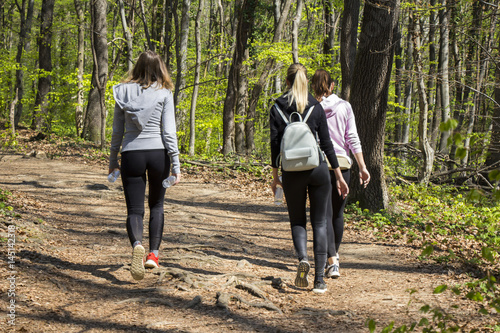 Three young girls walking in spring forest - 145142318