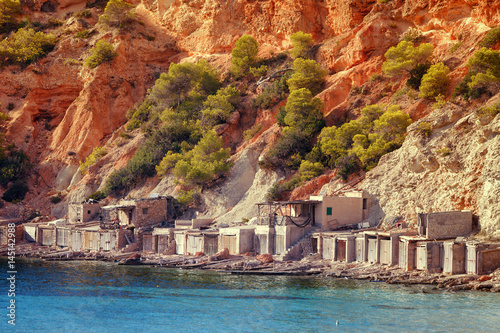 Old fishing huts where they keep the run of fishing vessels in the Caleta Beach in Ibiza, with its red earth, Spain.