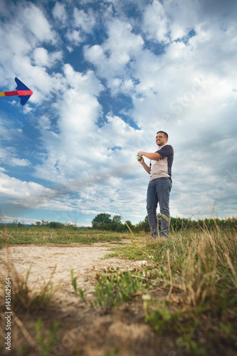 Low angle view of young man flying a kite on a meadow on a cloudy windy day