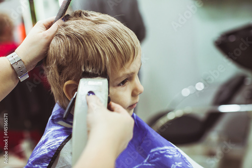 Little boy makes hairstyle at the hairdresser