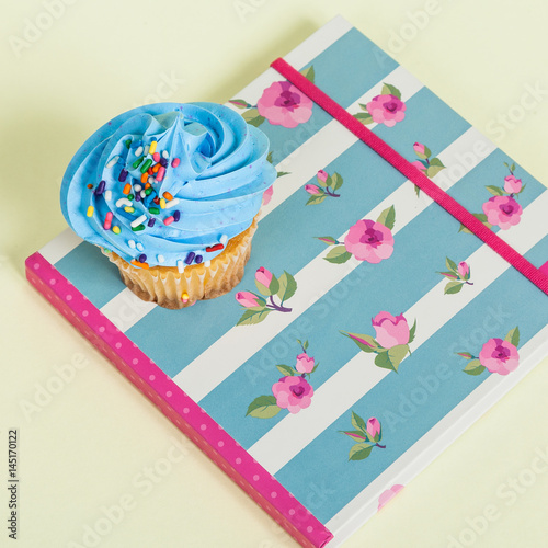 Tasty cupcake on notebook Poster