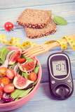 Fruit and vegetable salad and glucometer with tape measure, concept of diabetes, slimming and healthy nutrition