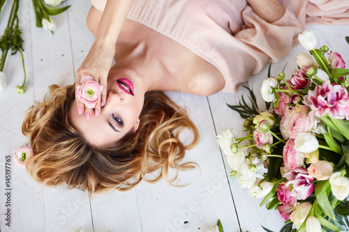Fototapeta Portrait of a young blonde woman in flowers. Woman's face with make-up and hairstyle