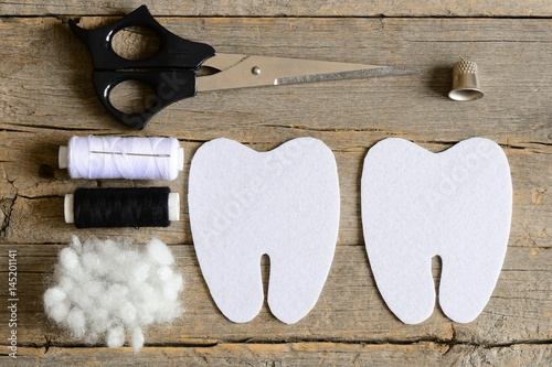Making a felt tooth fairy. Step. Instruction. Cut felt parts to make a felt tooth fairy. Scissors, thread, thimble, needle, filler on vintage wooden table. Handmade diy for children. Top view. Closeup