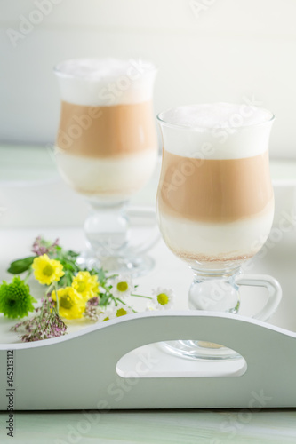 Two latte coffee with spring flowers on white table