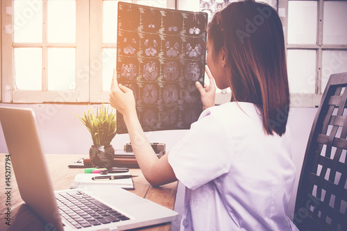 close up of female doctor holding x-ray or roentgen image , Check brain in clinic Poster