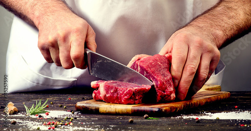 Wall mural Man cutting beef meat