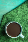 Cup of hot chocolate on green and teal textures