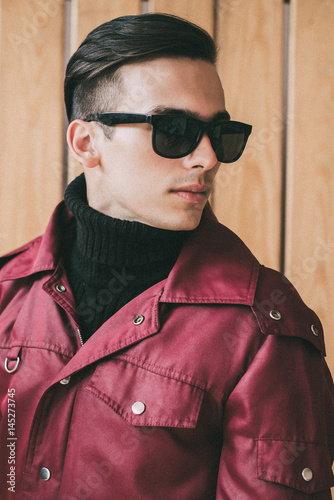 Poster Handsome young man looks toward in black glasses on wood background
