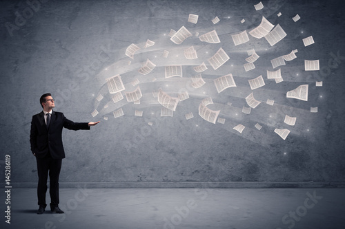 Caucasian businessman holding newspapers