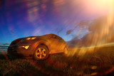 Car in the field at sunset