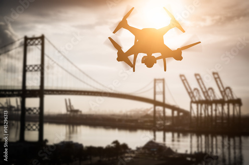 Plakat Silhouette of Unmanned Aircraft System (UAV) Quadcopter Drone In The Air Over Shipping Port