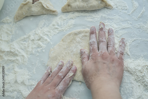 Preparing dough. Baking peremech concept. Flour, dough and meat cooking ingredients. Hands top view of cooking.