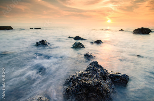 Fotobehang Koraalriffen Stunning sunset moment seascape,soft wave hitting the rock over cloudy sky. infinity focus and long exposure shot