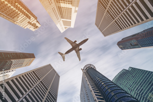 Airplane flying over city business buildings, high-rise skyscrapers Poster