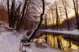 Scenery of wild river with sunset sky reflection in the mountains, in winter
