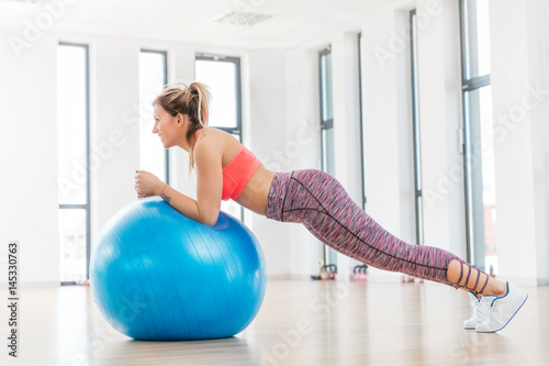Póster Young woman training with fitball at fitness club.