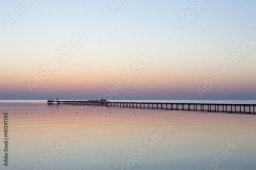 Poster Wschód słońca nad morzem z niebem odbijającym się na wodzie, z drewnianym molo, w zimnych barwach