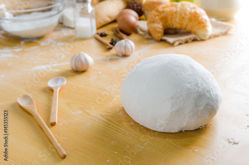 Close up shot of dough with bakery ingredients on wooden table shallow depth of field
