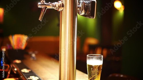 Vertical panoramic video of a beer glass on a counter in a pub or restaurant, next to a beer tap.