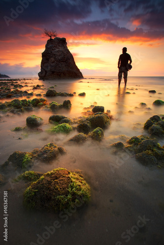 Silhouette of a man on the beach at sunset Poster