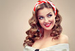 Beautiful retro vintage pin-up girl . Beautiful girl  with curly hair  pointing to the side . Presenting your product. Expressive facial expressions