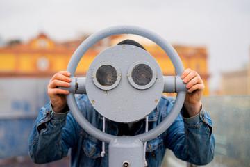 fun ideas. man looks through his binoculars on the lookout closeup