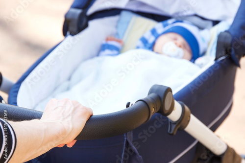 Poster Hand of woman holding babies pram with newborn baby sleeping inside