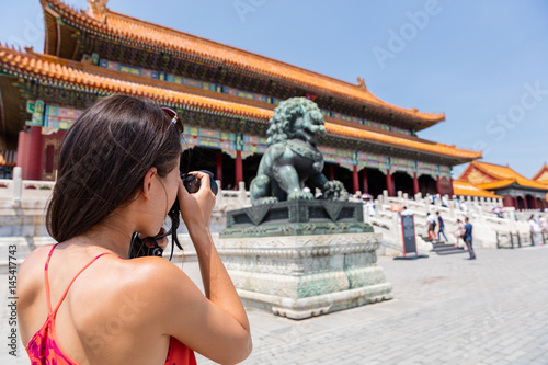 Fotobehang Peking Tourist photographer taking pictures with camera of sculpture in front of ancient chinese temple, china. Asia summer travel, tourism destination popular attraction