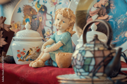 ceramic girl figurine and porcelain vase in sunday flea market. Antique bazaar