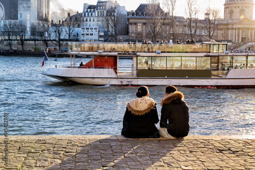 Wall mural Paris young couple sits on the bank of the Seine to watch the sunset and a river boat going by
