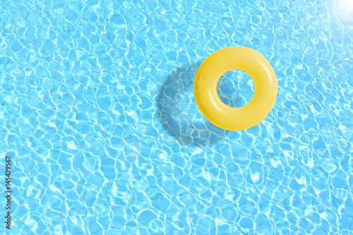 mata magnetyczna yellow swimming pool ring float in blue water. concept color summer.