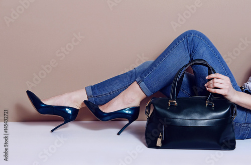 Plakat female legs lies in jeans blue lacquered heel shoes and big bag
