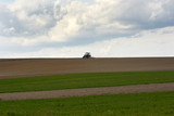tractor at work cultivating a field in spring, farmland, plowed field,